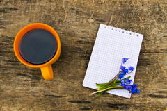 Cup of coffee with notepad and blue scilla flowers on wooden desk Royalty Free Stock Photos
