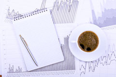 Cup of coffee, notepad  and graphs Stock Photo