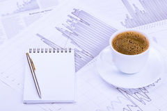 Cup of coffee, notepad  and graphs Royalty Free Stock Photo