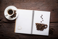 Cup of coffee. Notepad with cup of coffee made of beans and espresso on wooden desk Royalty Free Stock Image