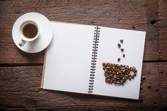 Cup of coffee. Notepad with cup of coffee made of beans and espresso on wooden desk Stock Photography