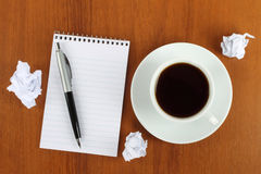 Cup of coffee with notepad, pen and crumpled paper Stock Images