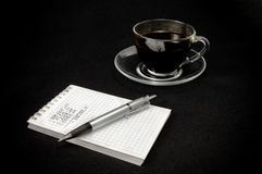 Cup of coffee and a notepad with a pen on a dark b Royalty Free Stock Photos