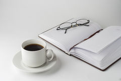 A cup of coffee with notepad on a white table. Royalty Free Stock Photo