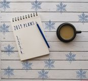 A cup of coffee and notepad on white wooden table. royalty free stock photography