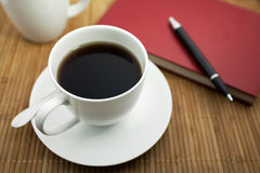 A cup of coffee and a notepad. On wood desk Stock Photos