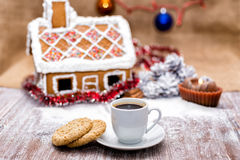 Cup of coffee and oatmeal cookies. On a background of traditional gingerbread house Stock Image