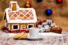 Cup of coffee and oatmeal cookies. On a background of traditional gingerbread house Royalty Free Stock Photography