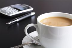 Cup of coffee in the office. Cup of coffee in the business office showing success Royalty Free Stock Image