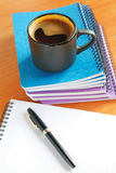 Cup of coffee on the office desk with notebook Stock Images