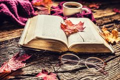 Cup of coffee old book glasses and autumn leaves. Royalty Free Stock Images