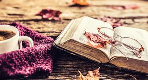 Cup of coffee old book glasses and autumn leaves. Royalty Free Stock Image