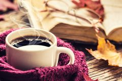 Cup of coffee old book glasses and autumn leaves. stock image