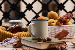 Cup of coffee old book glasses and autumn leaves with fruit bask stock photo