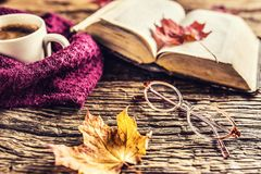 Cup of coffee old book glasses and autumn leaves. Royalty Free Stock Photos