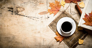 Cup of coffee with an old book and maple leaves. Stock Images