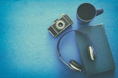 cup of coffee, old book, vintage photo camera and headphones Royalty Free Stock Photography