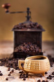 A cup of coffee and old coffee grinder Stock Image