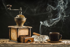 A cup of coffee with an old grinder and smoking a cigar in the background Royalty Free Stock Photo