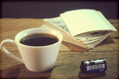 Cup of coffee and old paper photo frame on wood background Stock Images