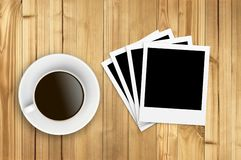 Cup of coffee and old photo paper on wooden Royalty Free Stock Image