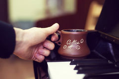 Cup of coffee on an old piano keyboard while composing. Evening time and some sun rays. Coffee mug on the piano keyboard. Cup of coffee on an old piano keyboard royalty free stock photos