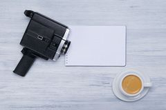A cup of coffee and an old video camera, lies on a white notepad for writing stock photography