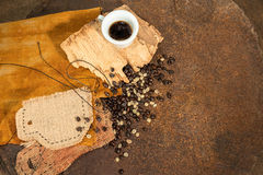 A cup of coffee with old wood and coffee beans on rusty texture. A cup of black coffee with an other  cup sewn in jute and some coffee beans placed with old Stock Photography
