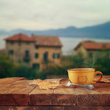 Cup of coffee on old wooden table in front of romantic Provence rural landscape. retro filtered image Stock Image
