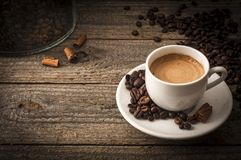 Cup of coffee on wooden table with cinnamon. A cup of coffee on old wooden table with some beans and some cinnamon`s sticks stock photos