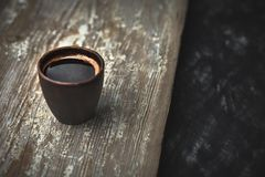 A clay cup with coffee on an old worn table. Stock Image
