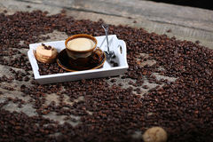 Cup of coffee and one cake. Coffee beans in a coffee cup and some cake, one macaron cake Royalty Free Stock Image