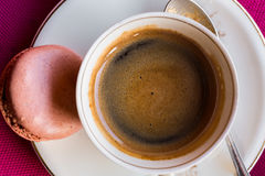Cup of coffee and one French macaroon Stock Images