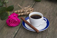 Cup of coffee, one rose, linking of cookies on a wooden table, a Royalty Free Stock Photo