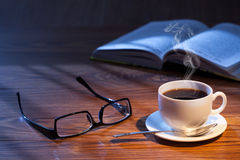 Cup of coffee, open book and glasses on a desk. Royalty Free Stock Images