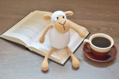 Cup of coffee with open book and toy on it stock photography