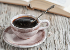 Cup of coffee and open book Stock Images
