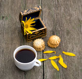 Cup of coffee, open casket with a flower, two linking of cookies Stock Photos