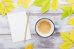 Cup of coffee, open empty notebook and autumn leaves on vintage wooden table top view. Cozy breakfast. Fall bucket list. Flat lay Stock Photos