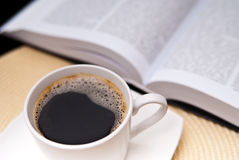 Cup of coffee and opened book Stock Images
