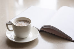 Cup of coffee and opened book Stock Image