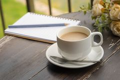 Cup of coffee and opened notebook on wooden table Stock Photography