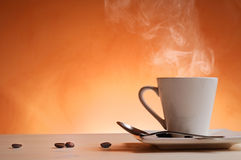 Cup of coffee with orange background front view Stock Image