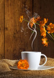 Cup of coffee with orange flowers. On wooden background Royalty Free Stock Images