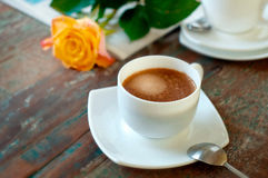 Cup of coffee and orange rose on vintage wood Royalty Free Stock Images