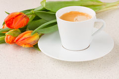 Cup of coffee with orange tulips Stock Photos