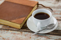 Cup of coffee with organiser on wooden table. Close-up of black coffee with organiser on wooden table Royalty Free Stock Photos