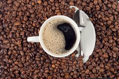 Cup of coffee over a lot of coffee beans Stock Photos