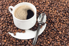 Cup of coffee over a lot of coffee beans Stock Images