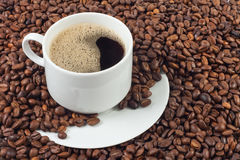 Cup of coffee over a lot of coffee beans Stock Photography